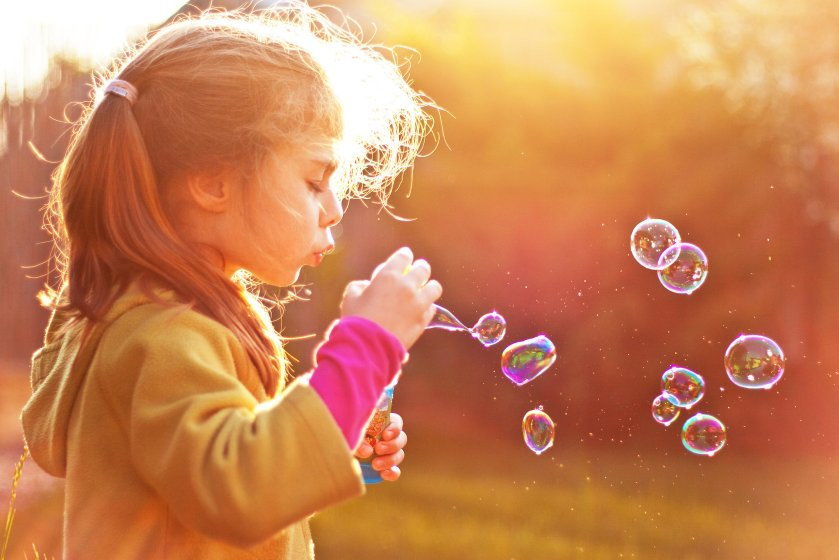 A girl playing with bubbles.
